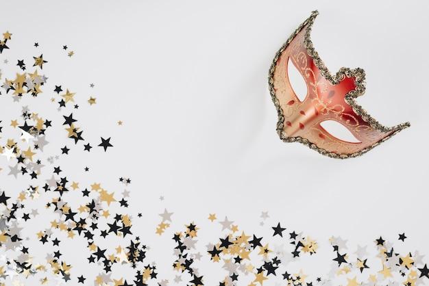 Máscara de carnaval com lantejoulas na mesa Foto gratuita