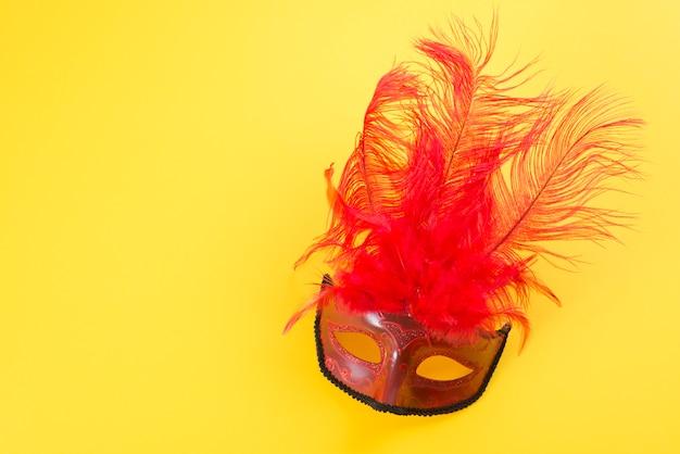 Máscara de carnaval com penas na mesa Foto gratuita