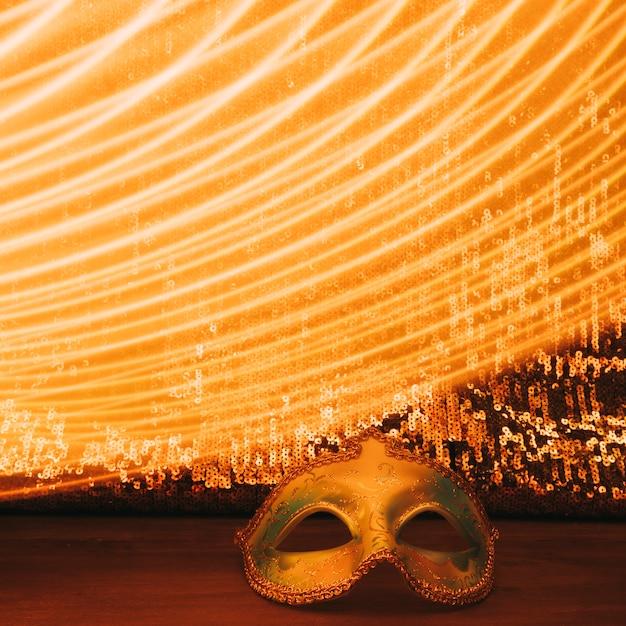 Máscara de carnaval em frente a tecido de lantejoulas cintilante com luzes curvas Foto gratuita