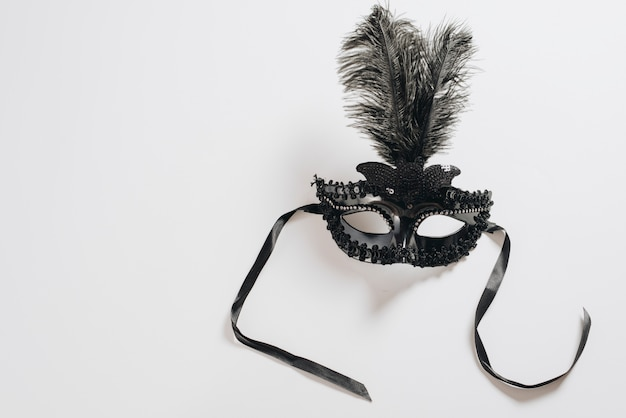 Máscara de carnaval escuro com penas na mesa Foto gratuita
