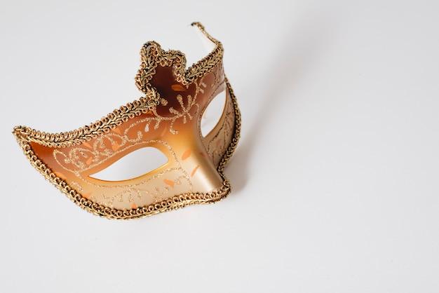 Máscara de carnaval laranja na mesa de luz Foto gratuita
