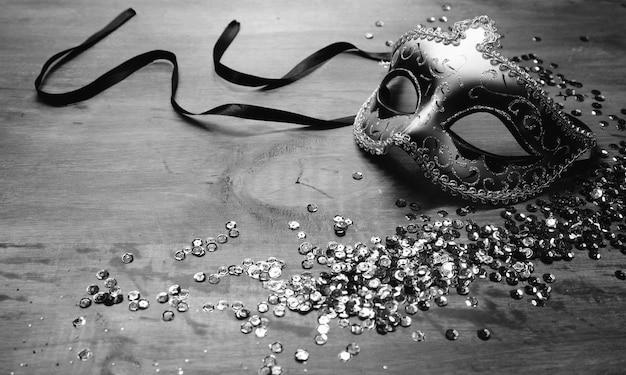 Máscara de carnaval veneziano com lantejoulas na mesa de madeira Foto gratuita