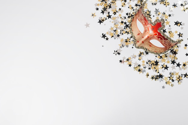Máscara de carnaval vermelho com lantejoulas na mesa Foto gratuita