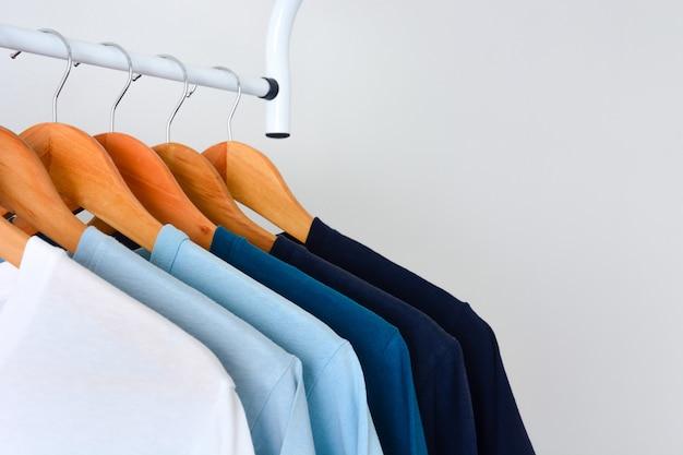 Máscara de coleção de cores de tons de azul camisetas suspensão de roupas de madeira em rack de roupas Foto Premium