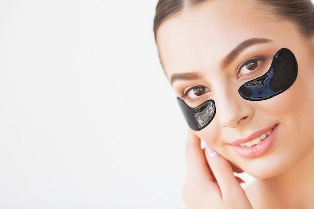 Máscara de cuidados com a pele. mulher, com, pretas, remendos Foto Premium