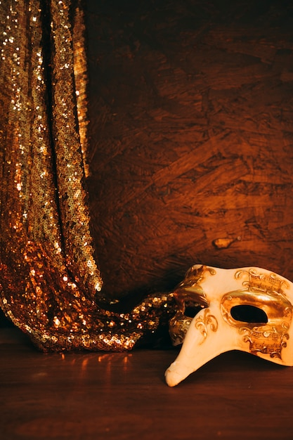 Máscara de disfarce branco com tecido de lantejoulas douradas de suspensão contra o plano de fundo texturizado Foto gratuita