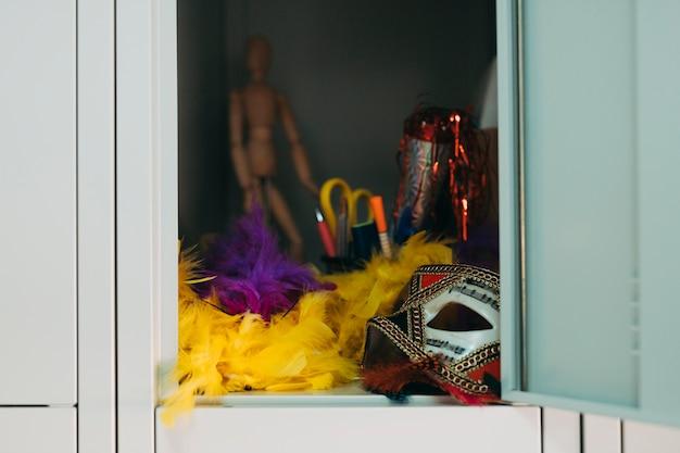Máscara de festa; boa de pena amarela e roxa no cacifo Foto gratuita