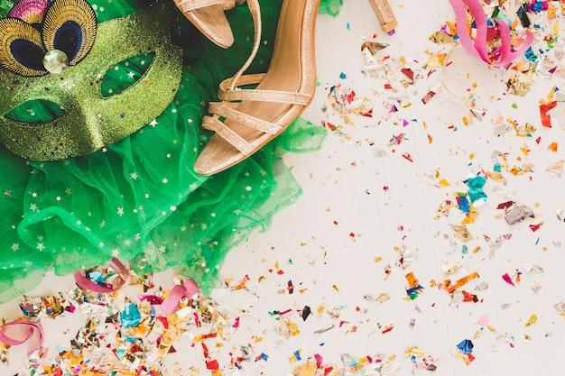 Máscara de festa e sapatos dourados em branco Foto gratuita