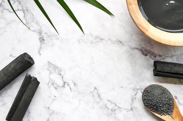 Máscara facial e esfoliação por pó de carvão ativado na mesa de mármore Foto Premium