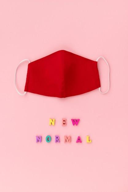 Máscara não médica cobrindo o rosto com inscrição novo normal Foto Premium