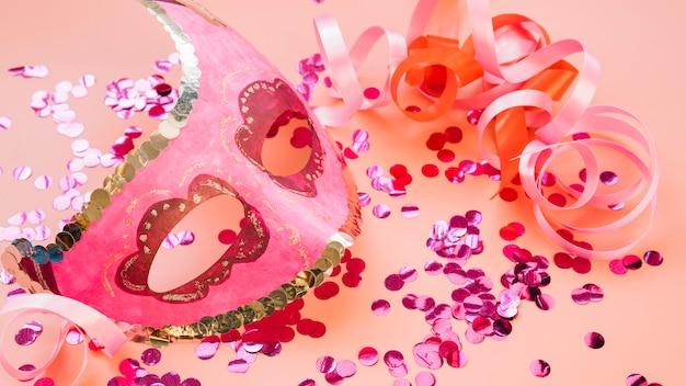 Máscara perto de fitas e conjunto de brilhos rosas Foto gratuita