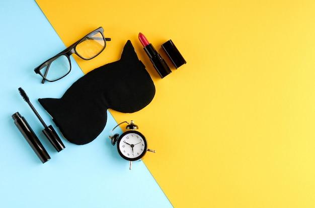 Máscara preta dos vidros, do despertador, do rímel, do pomade e do sono na superfície azul e amarela. Foto Premium