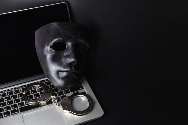 Máscara preta e algema no computador em preto Foto Premium