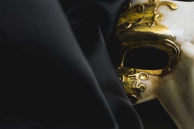 Máscara veneziana com um longo nariz em um tecido preto fechar-se Foto gratuita