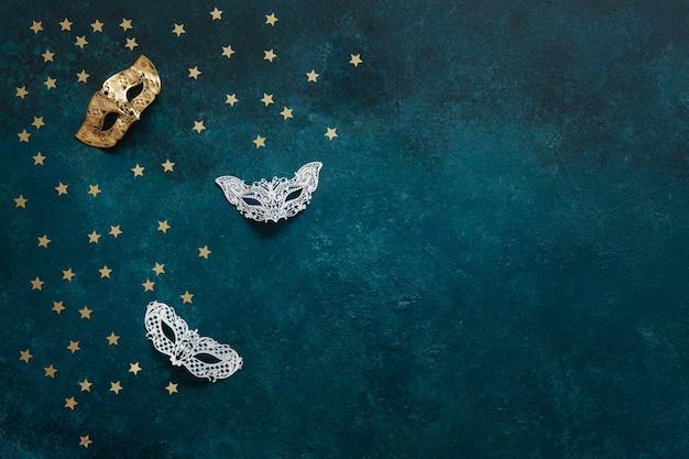 Máscaras de carnaval e confetes de glitter dourados. vista superior, cima, ligado, experiência azul Foto Premium
