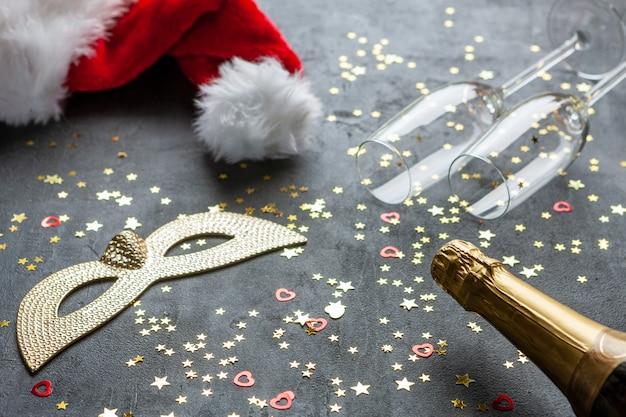 Máscaras de carnaval, garrafas de champanhe e chapéu vermelho do papai noel e duas taças de champanhe e confetes com glitter dourado, Foto Premium