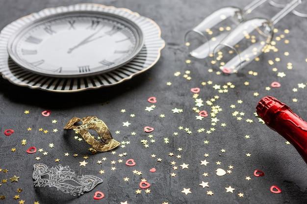 Máscaras de carnaval, garrafas de champanhe e duas taças de champanhe e confetes glitter dourados, vista superior, close-up em fundo cinza Foto Premium