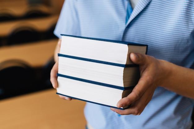 Masculinas mãos segurando uma pilha de livros. Foto Premium
