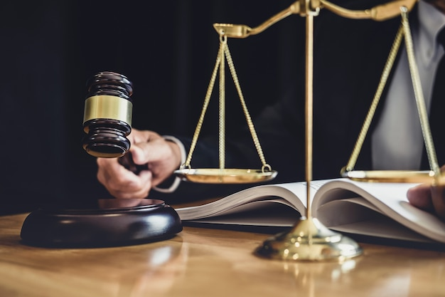 Masculino advogado ou juiz trabalhando com documentos de contrato, livros de direito e martelo de madeira na mesa no tribunal, advogados de justiça no escritório de advocacia, direito e conceito de serviços jurídicos Foto Premium