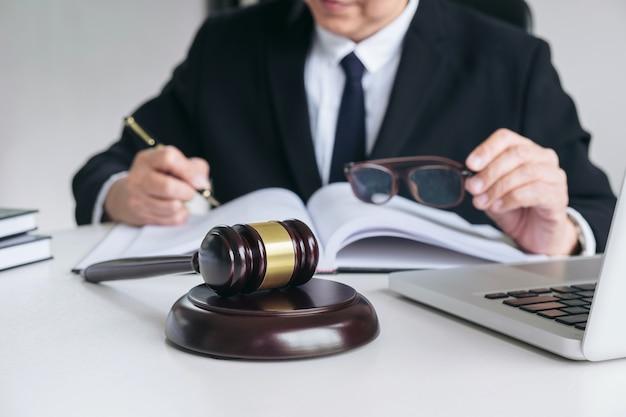 Masculino advogado ou juiz trabalhando com livros de direito Foto Premium