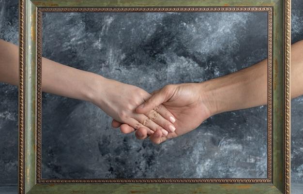 Masculino e feminino apertando as mãos no meio da moldura. Foto gratuita