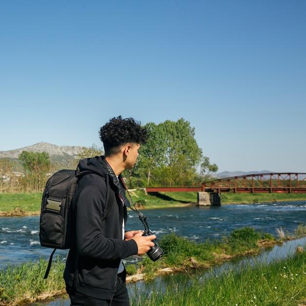 Masculino fotógrafo carregando mochila e câmera caminhadas perto do rio bonito Foto gratuita