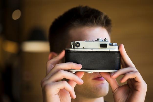 Masculino fotógrafo tirando foto com a câmera vintage Foto gratuita