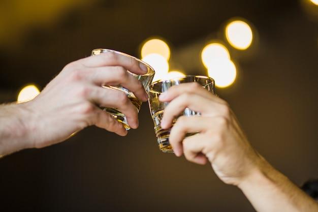 Masculino mão brindando o copo de bebidas contra o fundo iluminado bokeh Foto gratuita