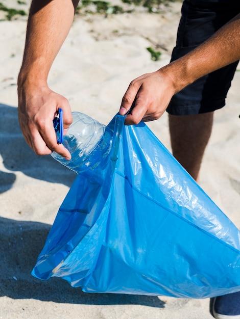 Masculino mão colocando garrafa de plástico transparente no saco de lixo azul Foto gratuita