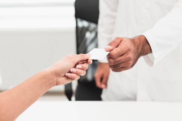 Masculino mão dando um cartão branco Foto gratuita