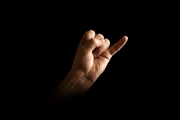 Masculino mão fazendo mindinho juro sinal sobre fundo escuro Foto Premium
