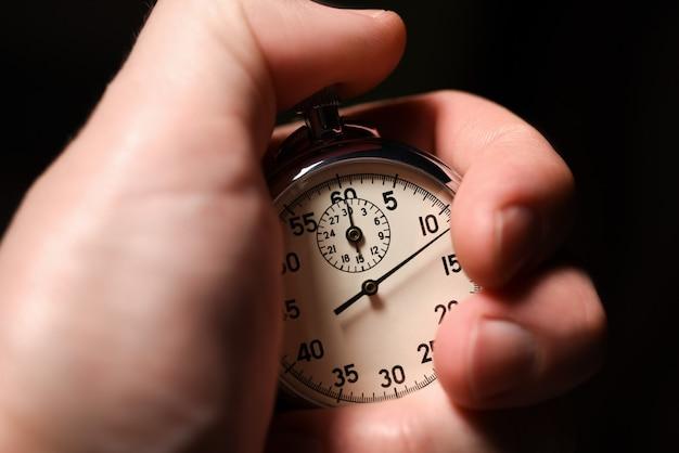 Masculino mão inicia o cronômetro analógico em um fundo preto, close-up, isolar Foto Premium