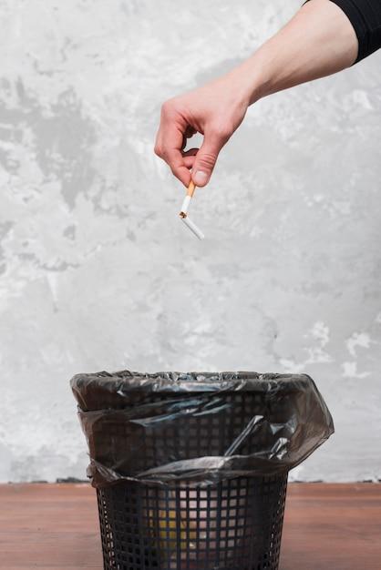 Masculino mão jogando cigarro quebrado para o caixote do lixo Foto gratuita