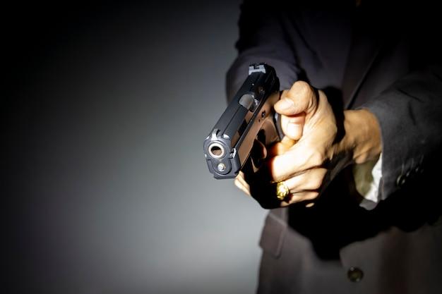 Masculino mão segurando a arma para atirar Foto Premium