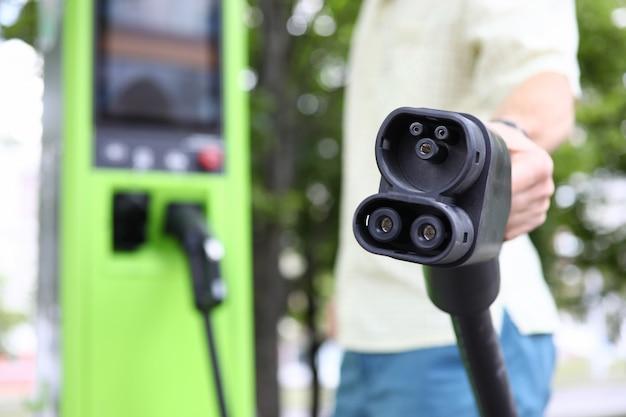 Masculino mão segurando o carro preto, cobrando o cabo do carro Foto Premium