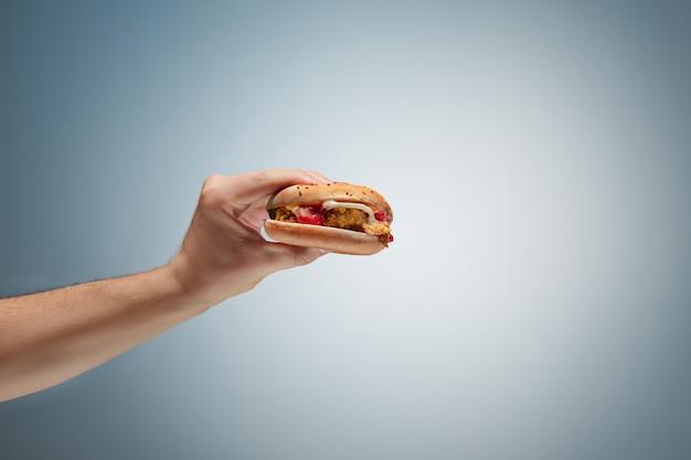 Masculino mão segurando saboroso hambúrguer Foto gratuita