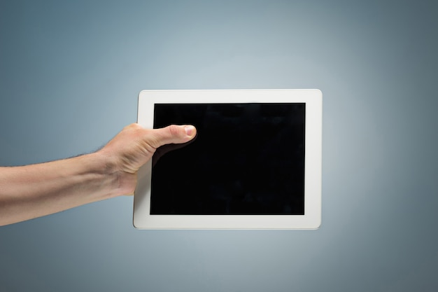 Masculino mão segurando um tablet Foto gratuita