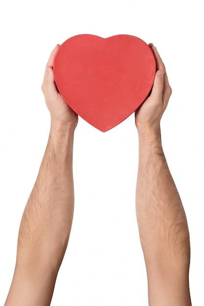Masculino mão segurando uma caixa vermelha em forma de um coração. Foto Premium