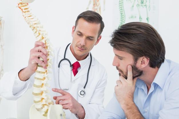 Masculino médico explicando a espinha a um paciente Foto Premium