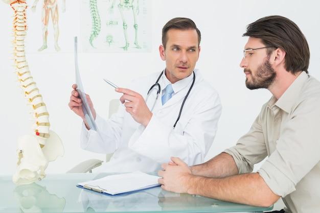 Masculino médico explicando xray da coluna para o paciente Foto Premium