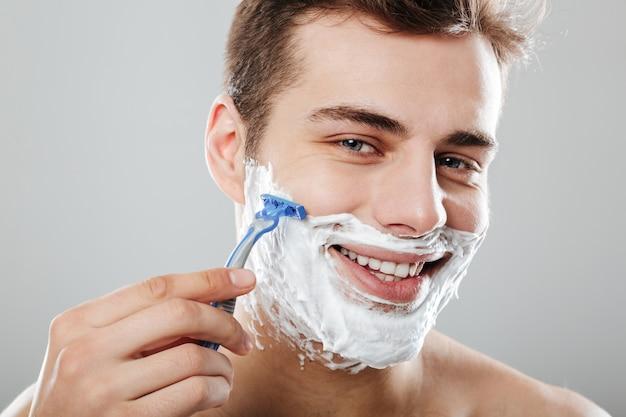 Masculino morena com cabelo curto escuro, barbear o rosto com navalha e gel ou creme, sendo satisfeito ao longo da parede cinza close-up Foto gratuita