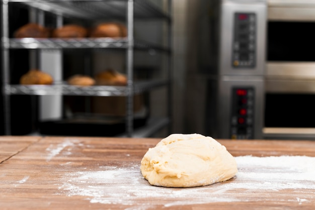 Massa amassada com farinha na mesa na padaria Foto gratuita