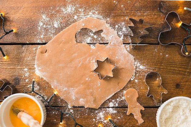 Massa com formas para biscoitos entre farinha Foto gratuita