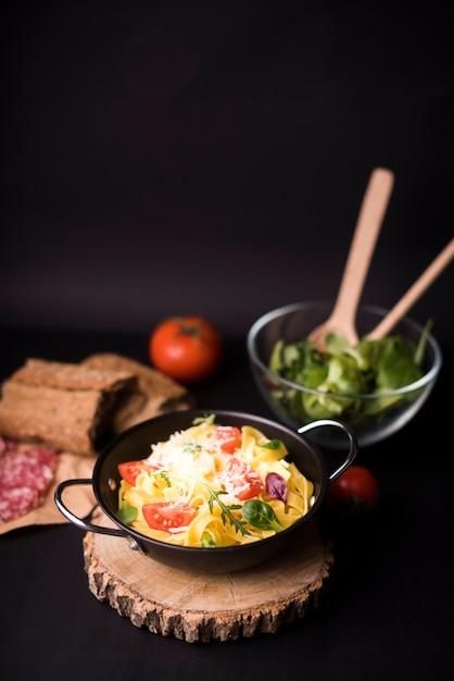 Massa cozida vegetal no potenciômetro de cozimento no coaster de madeira Foto gratuita