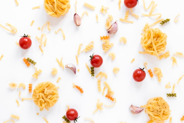 Massa crua e tomate cereja fresco sobre a superfície branca Foto gratuita