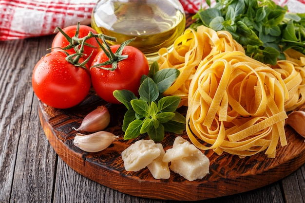 Massa crua e tomate em uma tábua Foto Premium