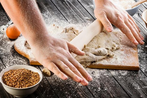 Massa de alongamento de baker com um rolo e farinha sobre a tábua de cortar na mesa de madeira Foto gratuita