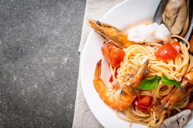 Massa de frutos do mar espaguete com amêijoas, camarão, squis, mexilhão e tomate Foto Premium