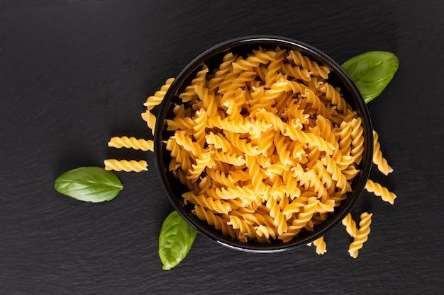 Massa de fusili italiana orgânica cru comida conceito em tigela preta na placa de ardósia preta com espaço de cópia Foto Premium