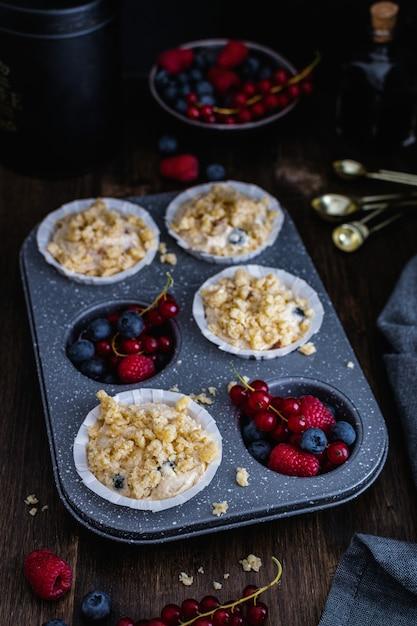 Massa de muffin cru com mirtilo, framboesa e groselha na mesa de madeira rústica Foto Premium